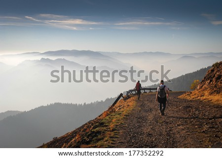 Group of people hiking in the mountains on a tourist track at sunset - stock photo