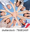 Group of people hold hands together across blue sky (focus on hands) - stock photo