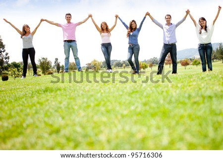 Group of people holding hands at the park and smiling - stock photo