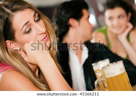 Group of people in a bar or restaurant drinking beer, woman in front being sad since her boyfriend is flirting with another girl dumping her - stock photo