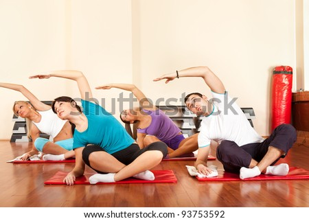 Group of people in a stretching class at the gym - stock photo