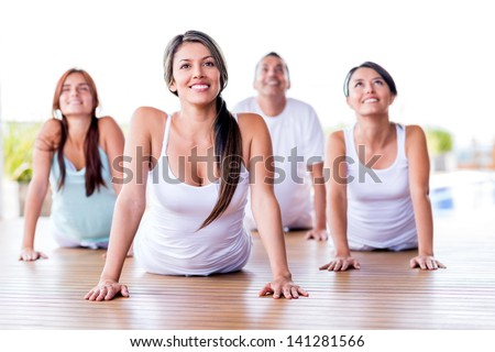 Group of people in a yoga class looking very happy - stock photo