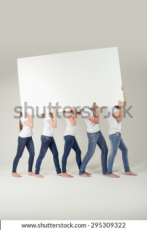 Group of People in Casual Outfits Carrying Empty White Large Board Over their Shoulders, Emphasizing Copy Space. Captured in Studio. - stock photo