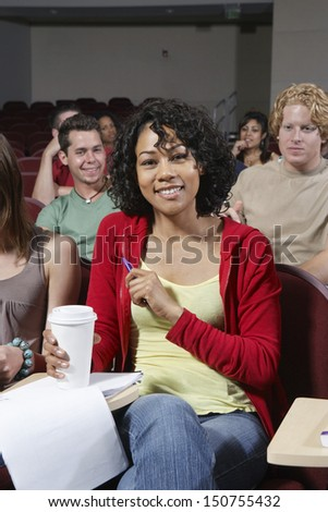 Group of people in classroom, woman in foreground - stock photo