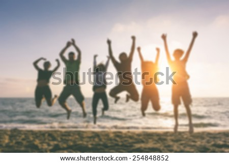 Group of people jumping at beach, blurred background. Backlight shot. Happiness, success, friendship and community concepts.