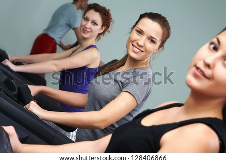 Group of people looking at camera while working out in gym - stock photo
