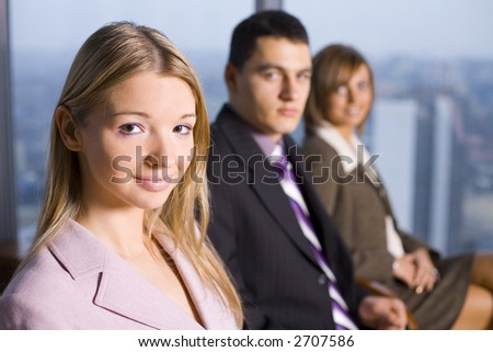 Group of People Looking at the Camera. Focus on first person's face. There's Big Window With Big City View Behind Them. - stock photo