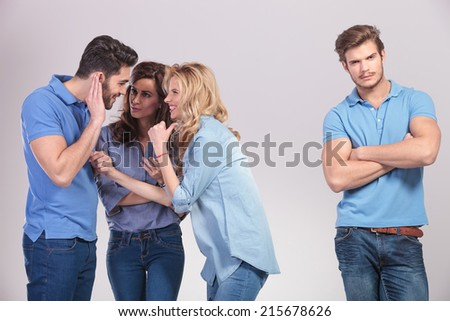 group of people making fun and gossip about their friend on grey studio background - stock photo