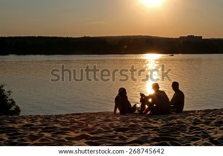 group of people on beach on sunset, group of people on a riverbank, picnic on a beach, people watching the sunset, Silhouettes of people on a beach at sunset - stock photo