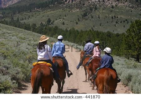 Group of people on horseback - stock photo
