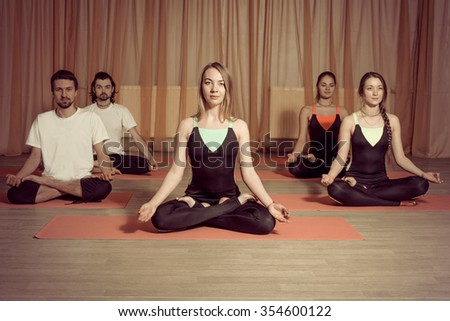 Group of people practicing yoga. They sit on the mat in the lotus position and meditate in the training room - stock photo