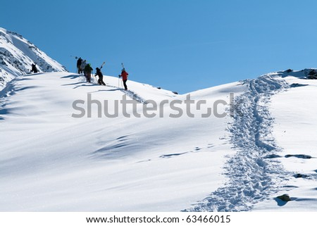 Group of people pro skiers and snowboarders walks on a mountain - stock photo