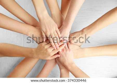 Group of people putting their hands together on wooden background
