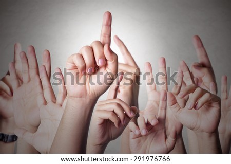 Group of people raising hands to answer a question - stock photo