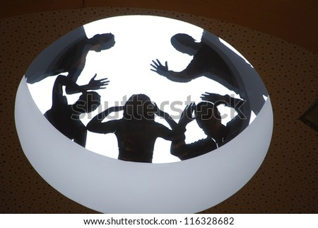 group of people silhouettes on rounded window - stock photo