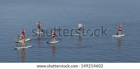 group of people stand up paddleboarding - stock photo