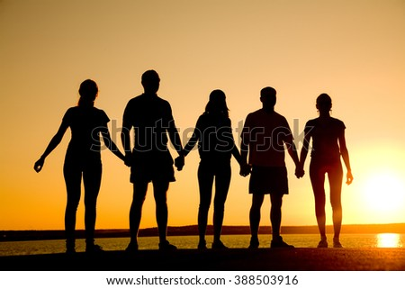 group of  people standing at the beach on  beautiful summer sunset - stock photo