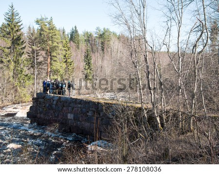 Group of people standing on the edge of a stone wall and looking at the raging river in a forest and blue sky - stock photo