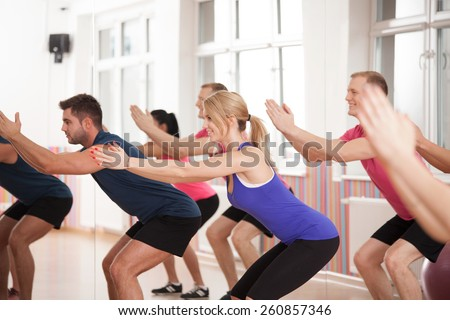 Group of people strengthening bottom muscles during fitness classes - stock photo