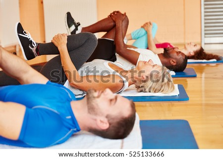 Group of people stretching during gymnastics course at fitness studio