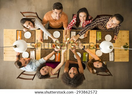 Group of people toasting and looking happy at a restaurant - stock photo