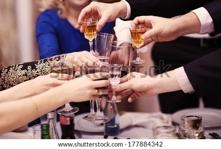 Group of people toasting at a celebration clinking their glasses together in congratulations , close up view of their hands. Film-like color correction. - stock photo
