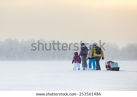 Group of people traveling over ice of frozen lake through the snowing at winter time - stock photo