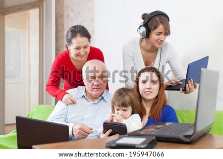 Group of people  uses few various electronic devices in home - stock photo