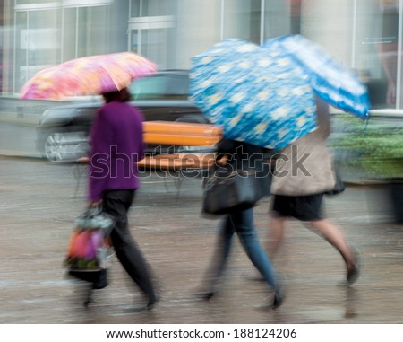 Group of people walking down the street in rainy day in motion blur - stock photo