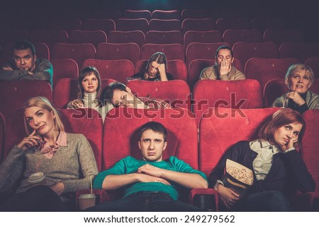 Group of people watching boring movie in cinema - stock photo