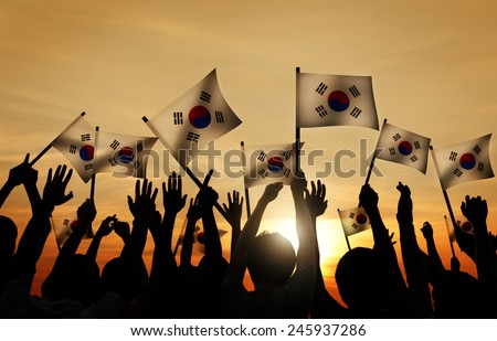 Group of People Waving South Korea Flags in Back Lit - stock photo