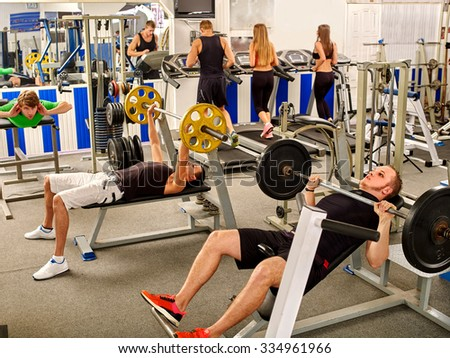 Group of people working on simulator his body at big gym.  - stock photo