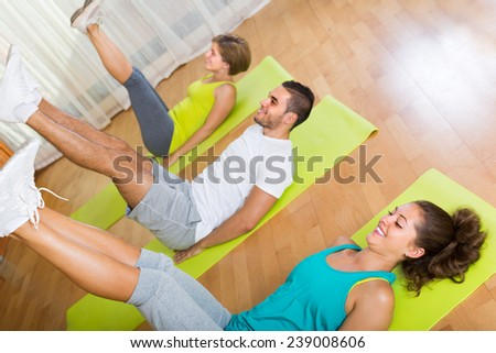 Group of positive adults training in fitness club. Focus on girl - stock photo