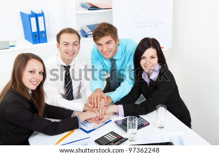 group of positive happy smile young business people pile of hands at desk office, businesspeople putting their hands on top of each other, meeting looking at camera, concept of team, working together - stock photo
