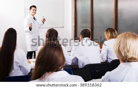 Group of positive professionals in white overalls at advanced training courses - stock photo