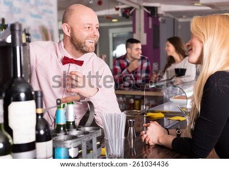 Group of positive smiling young adults hanging out in bar - stock photo