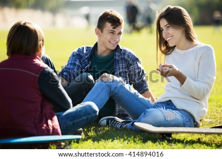 Group of positive teenage friends chatting and having fun outdoor. Focus on girl
