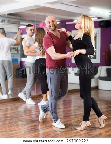 Group of positive young adults dancing at dance class  - stock photo