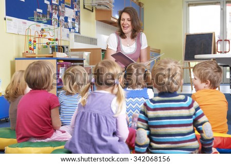 Group Of Pre School Children Listening To Teacher Reading Story - stock photo