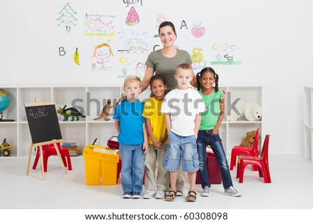 group of preschool kids and teacher in classroom - stock photo