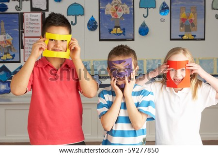 Group Of Primary School Children Cutting Out Paper Shapes In Craft Lesson - stock photo