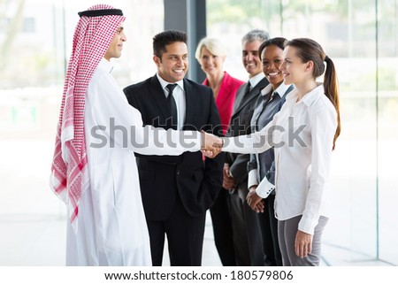 group of professional businesspeople welcoming Islamic businessman - stock photo