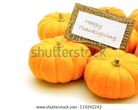 Group of pumpkins with Happy Thanksgiving card over white - stock photo