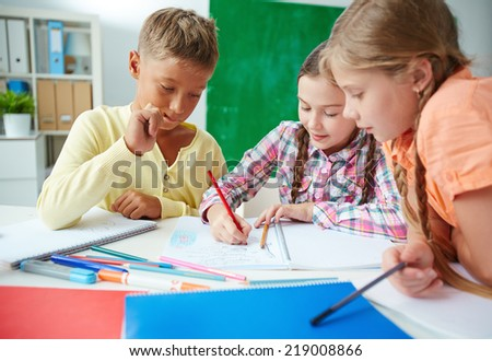 Group of pupils drawing together at lesson in junior school - stock photo
