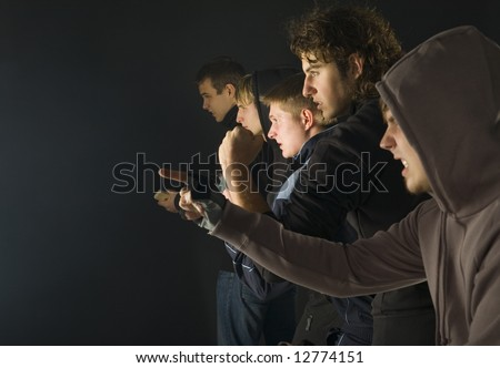 Group of ready to fight hooligans. One of them is screaming and pointing at something. Side view - stock photo