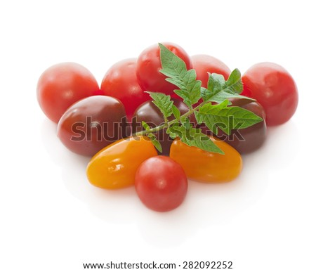 Group of red and yellow cherry tomatoes on a white background.