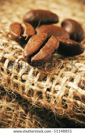 Group of roasted coffee beans close-up on burlap. Retro-stylized image.