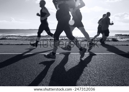 Group of runners compete in the race on coastal road - stock photo
