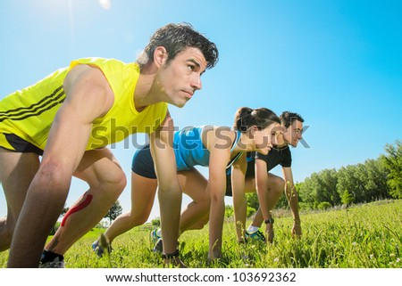 Group of runners ready for running challenge outdoors. Young athetes at the starting line ready to sprint and sport. Copyspace. - stock photo