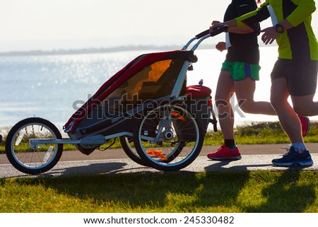 Group of runners with child, compete in the race on coastal road - stock photo